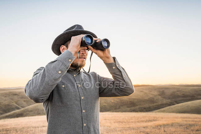 man-looking-through-binoculars